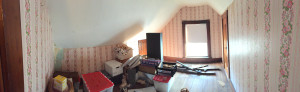Panoramic shot of a room with very pink wallpaper.